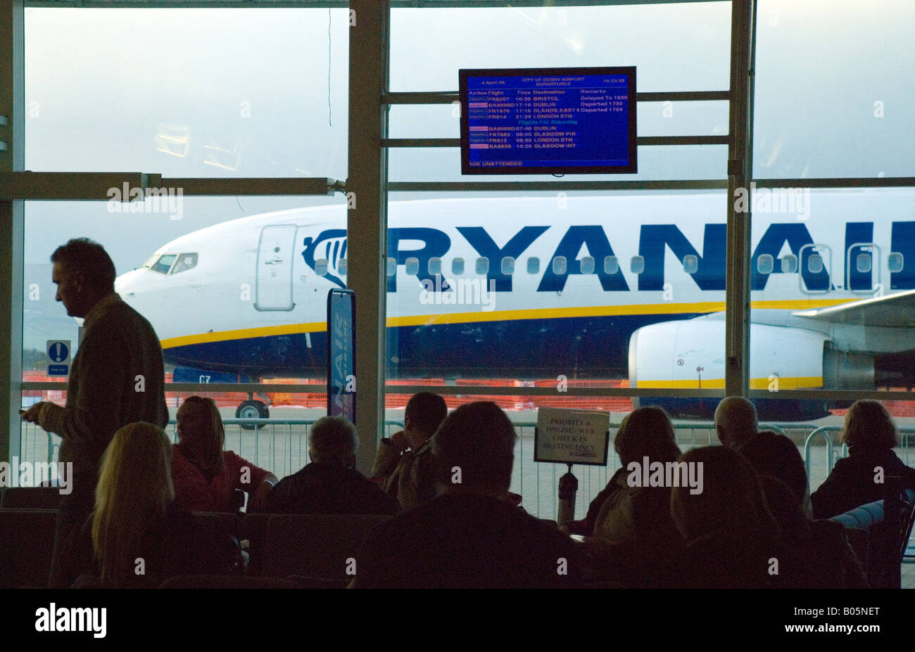 City of Derry Airport Northern Ireland Passengers in the departure lounge watch an aircraft taxi to the stand - Stock Image