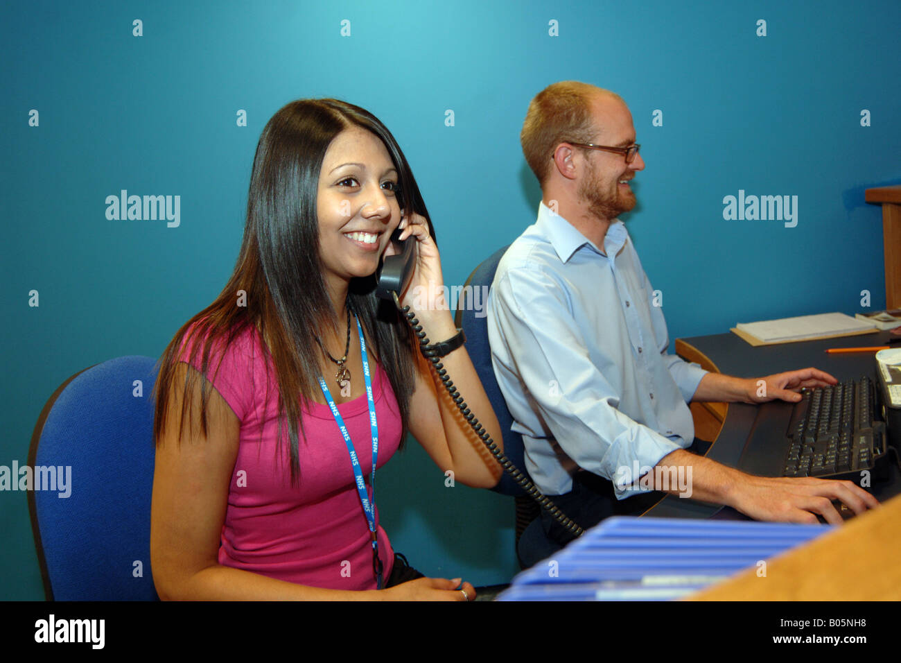 Office Receptionists work at the office reception of a large NHS office - Stock Image