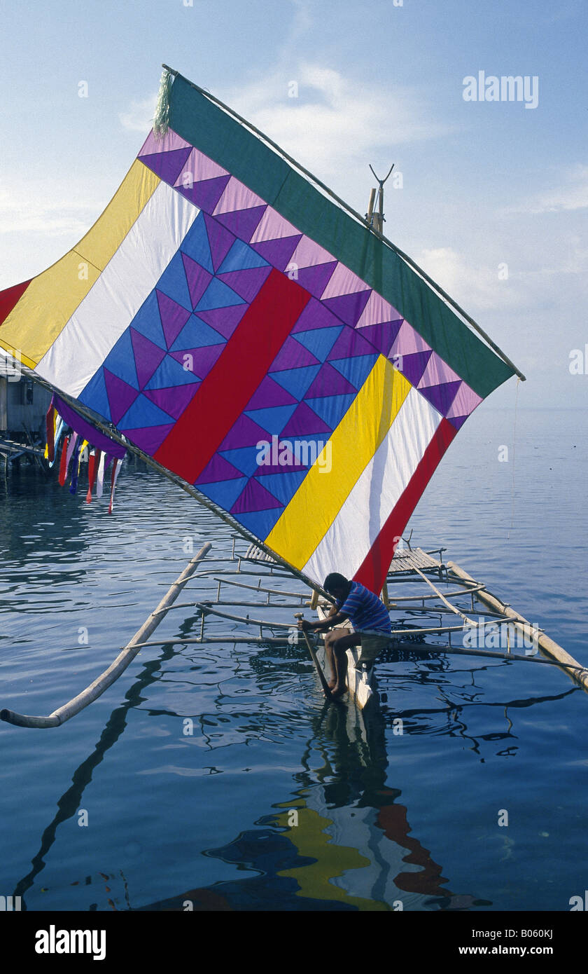 Sulu Sea Muslim vinta outrigger boat Colourful sail Two men ZAMBOANGA MINDANAO PHILIPPINES - Stock Image
