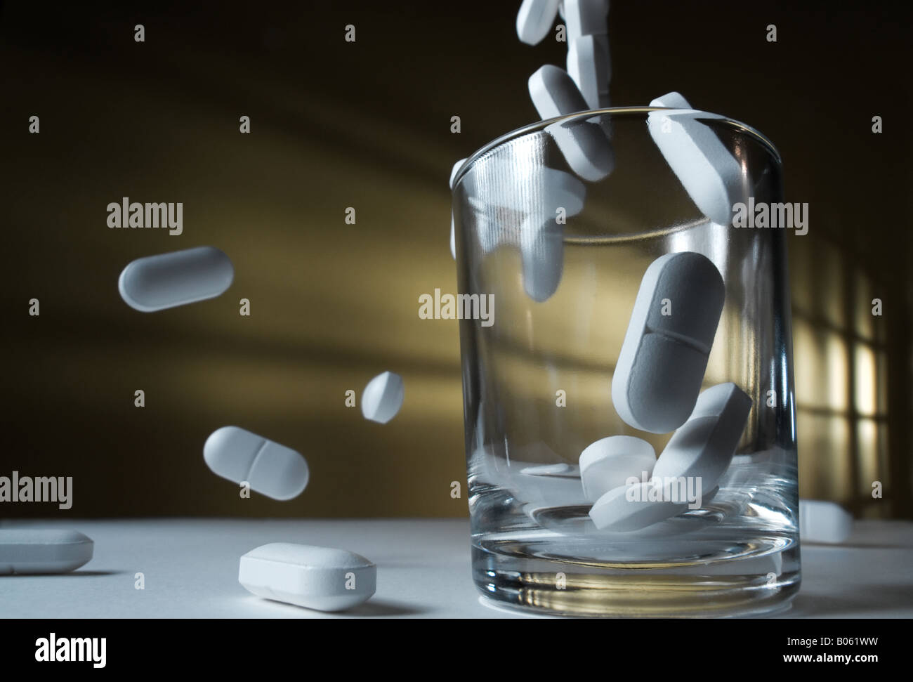 Pills falling to a glass and beyond - Stock Image