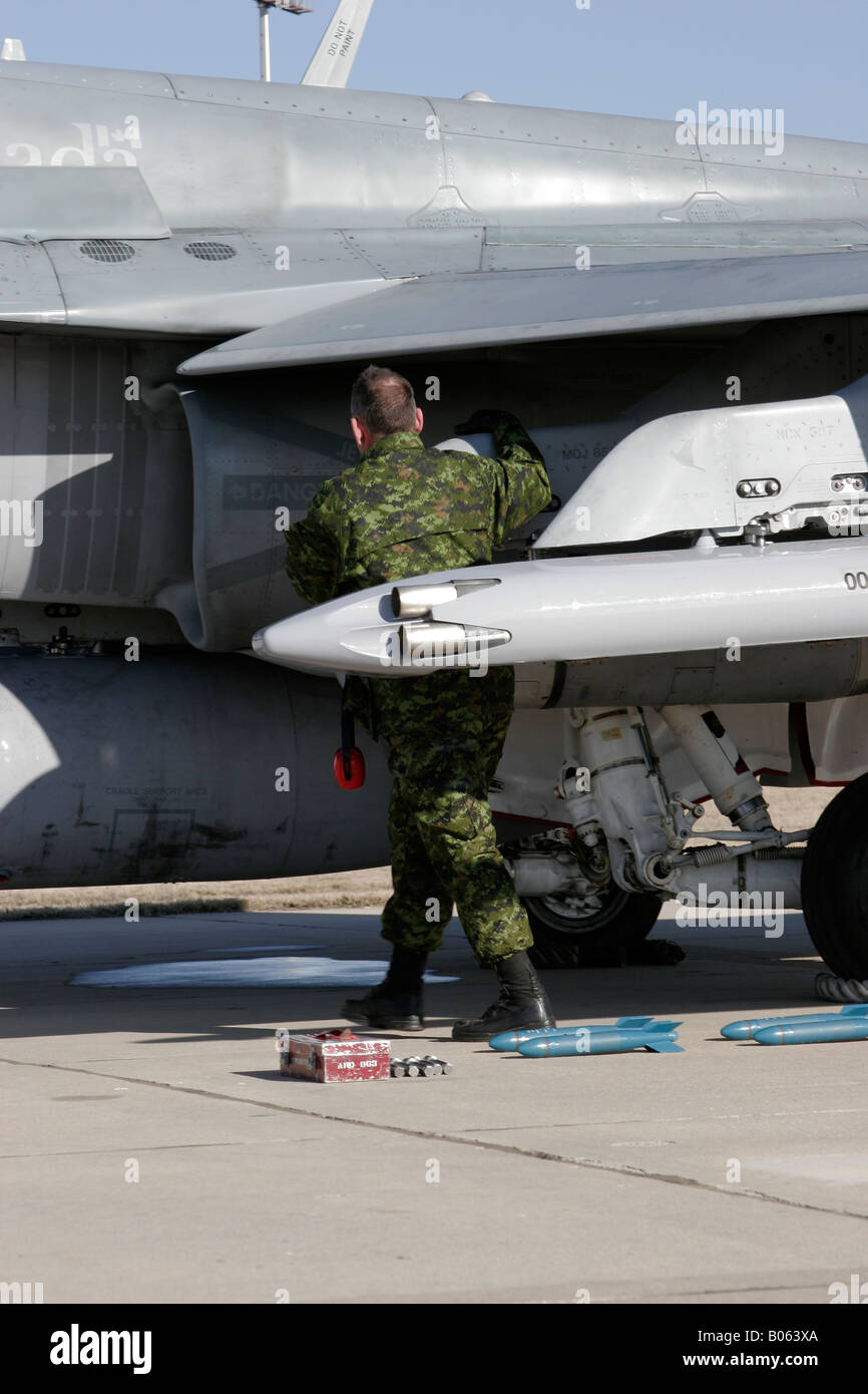 A ground crewman prepares a Canadian F A 18 hornet for flight Stock Photo