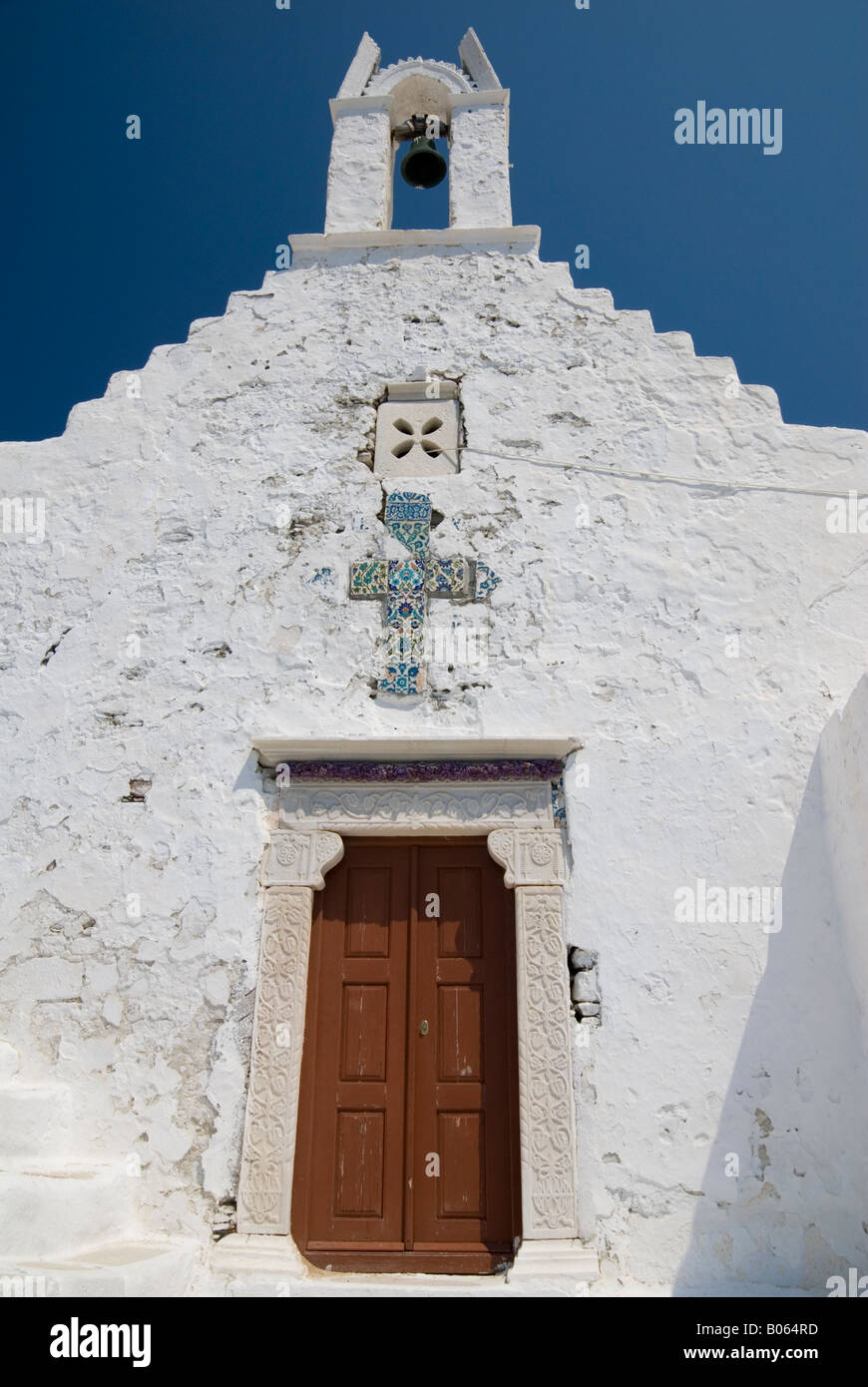 Whitewashed church of Agios Konstantinos with small bell tower and brown wooden door framed by engraved old marble - Stock Image