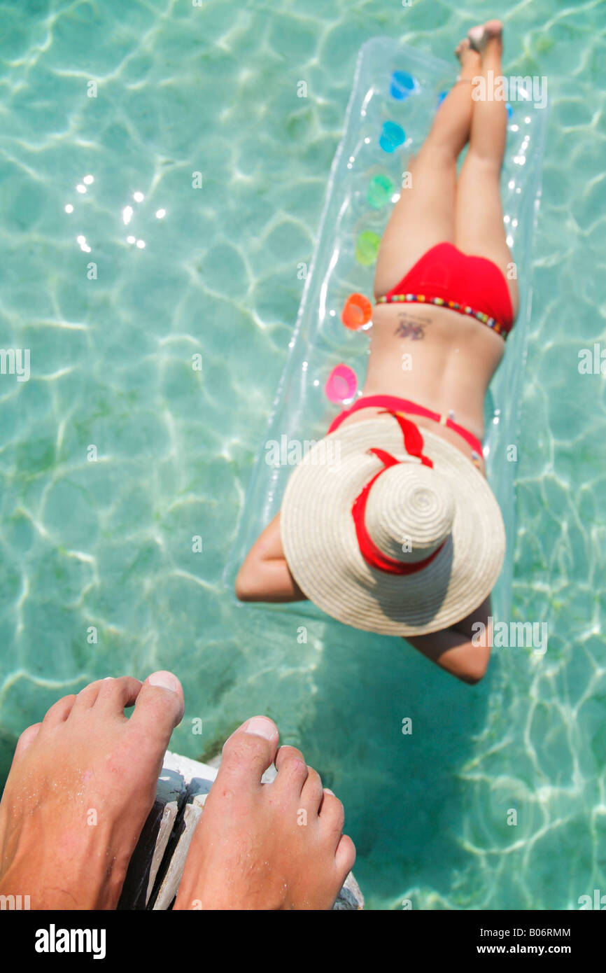 Woman floating on lilo in tropical lagoon with man above watching - Stock Image