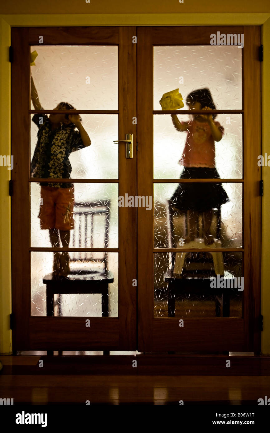 Six year old boy and his four year old sister balance precariously on chairs to reach up and dust a couple of doors - Stock Image