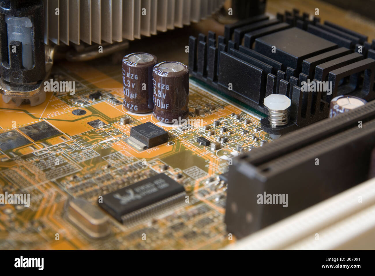twin electrolytic capacitors stand tall on the electronic motherboard main board of a modern era desktop computer - Stock Image