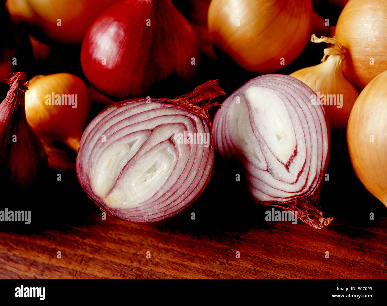 CUT RED ONION SURROUNDED BY WHOLE RED AND WHITE ONIONS ON A WOODEN SURFACE - Stock Image