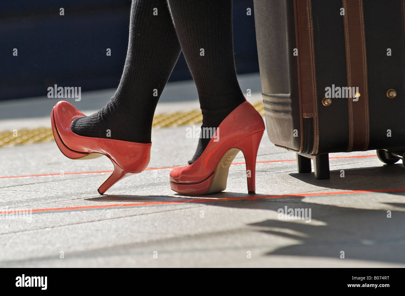 Bright pink shoes with high heels on a railway platorm. With suitcase - Stock Image