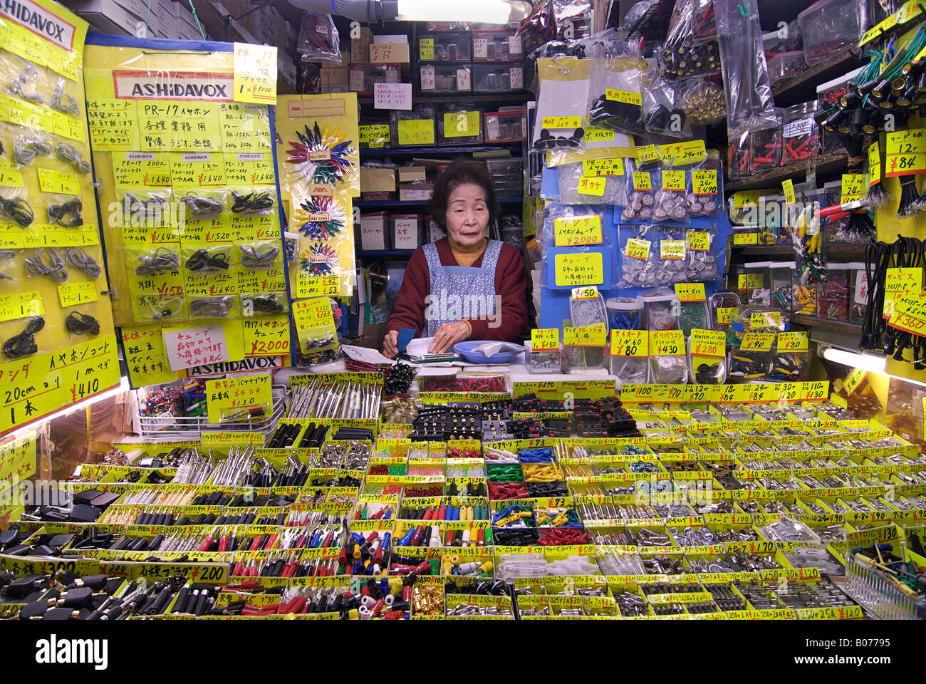 Elderly shopkeeper. Small electronics component retailer in the market at Akihabara, ELECTRIC TOWN, Tokyo, Japan - Stock Image