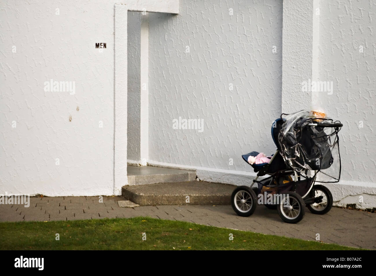 Push chair with baby left outside mens toilet in a public park New Zealand - Stock Image