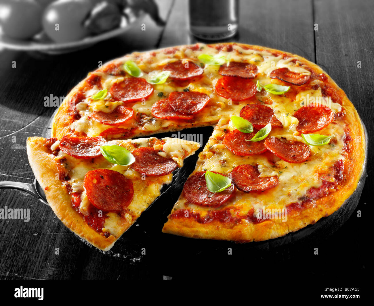 Rain crust pepperoni pizza with a slice out - Stock Image