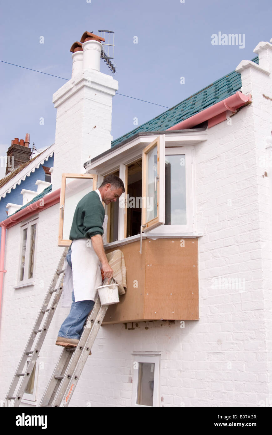 Man Painting exterior Window On House Up Ladder in the uk