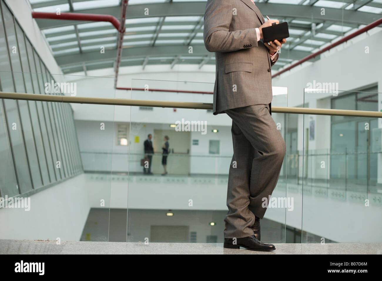 Businessman making notes in an office building - Stock Image