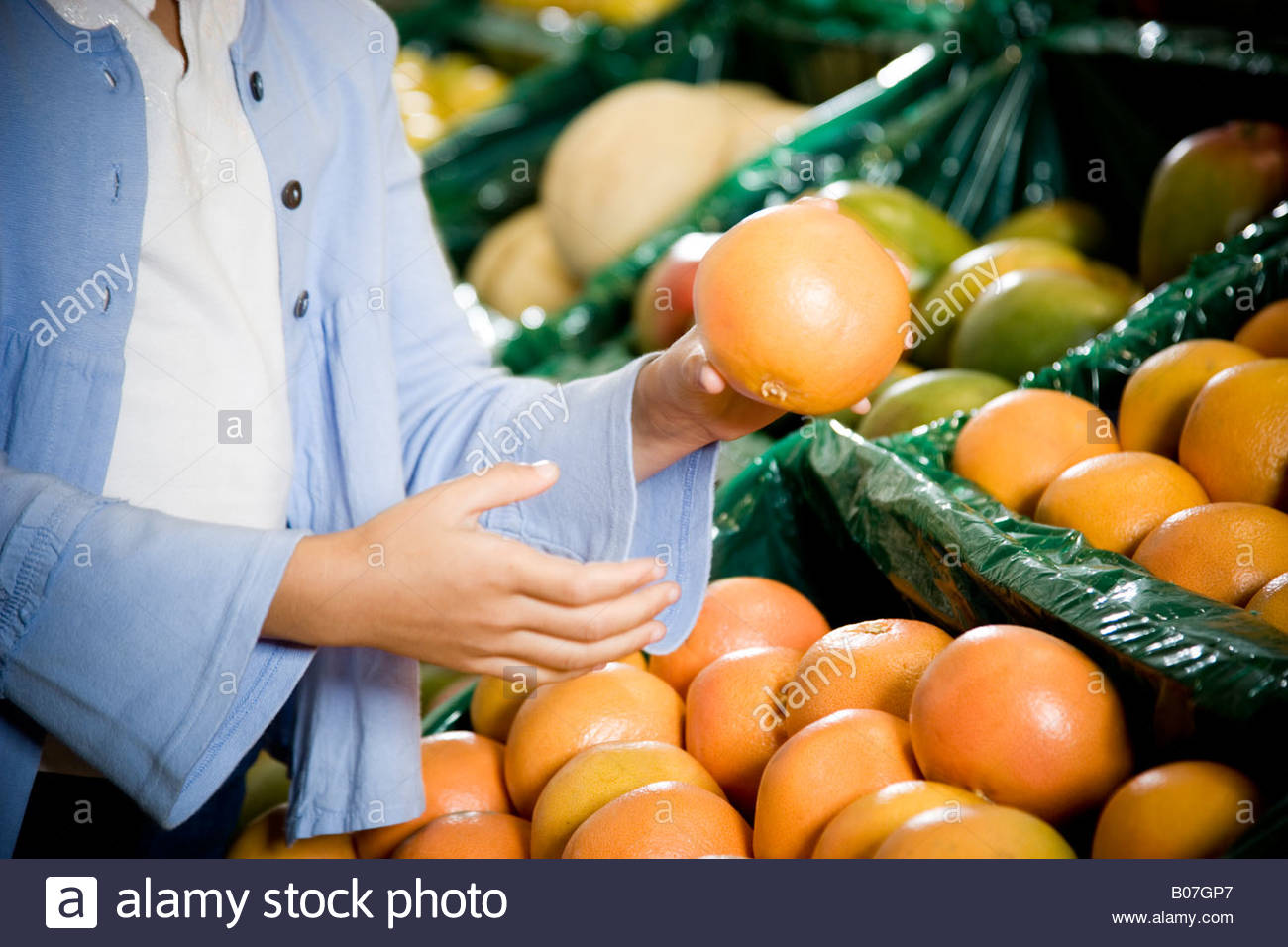 Cropped image of a girl selecting grapefruits in a supermarket. - Stock Image