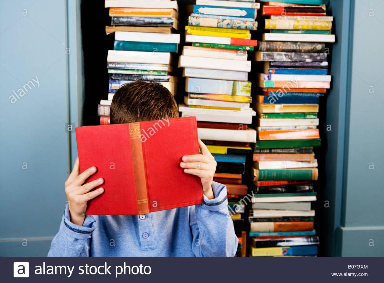 little boy hiding behind a book - Stock Image