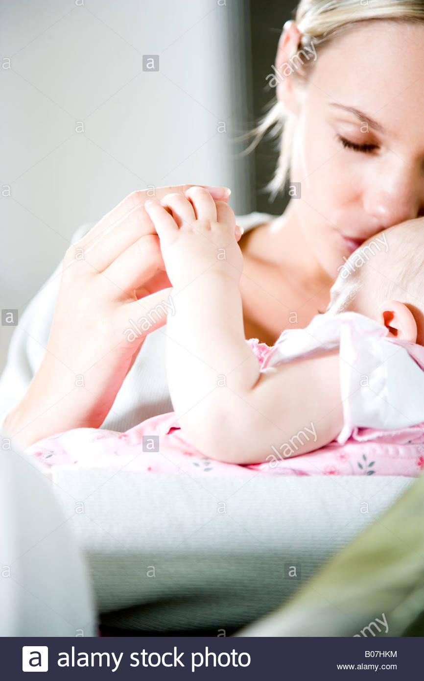 Mother kissing baby girl Stock Photo