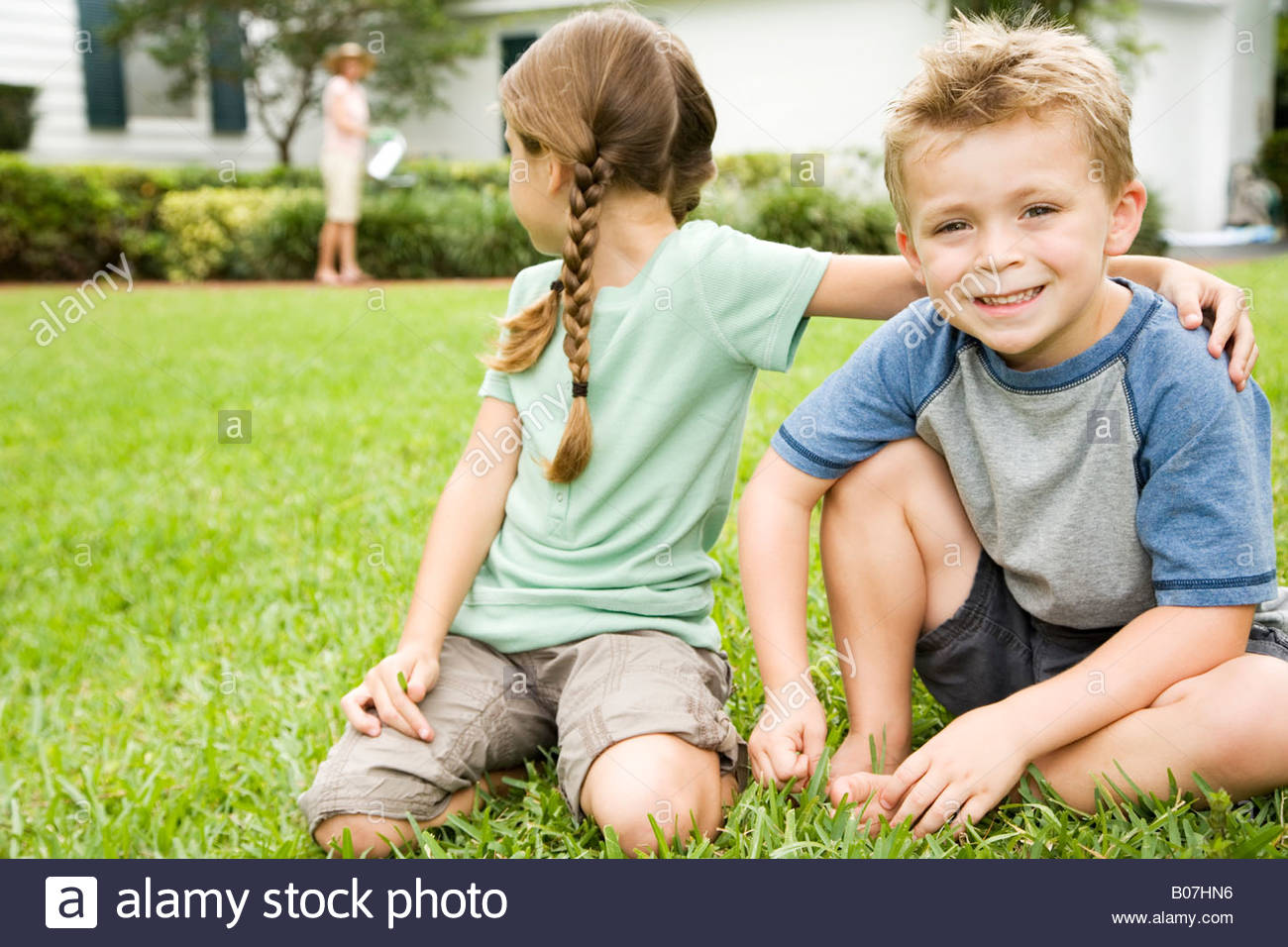girl and boy sitting on lawn, girl looking behind her - Stock Image