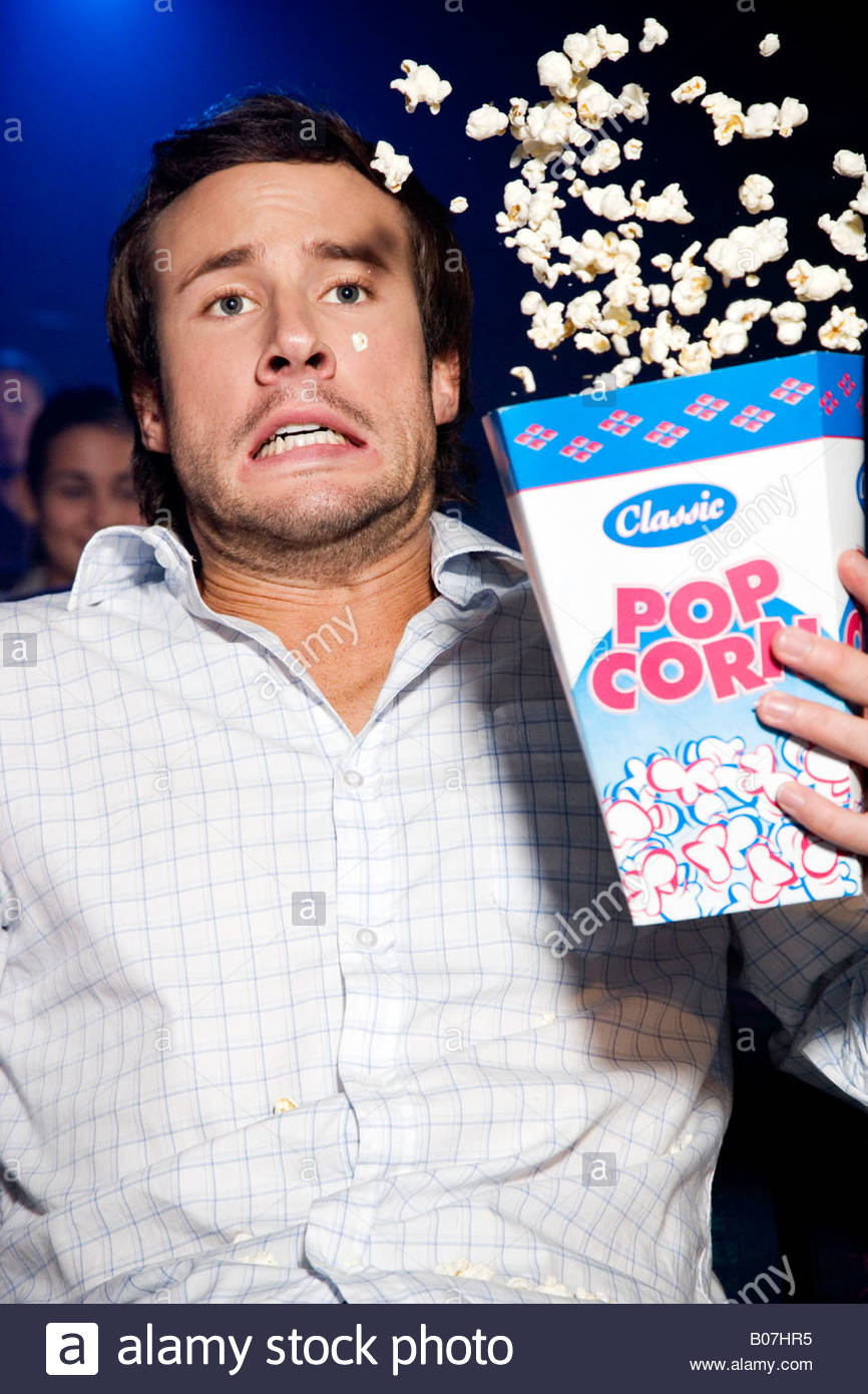 Man throwing his popcorn in the air in reaction to the film he's watching at the cinema Stock Photo