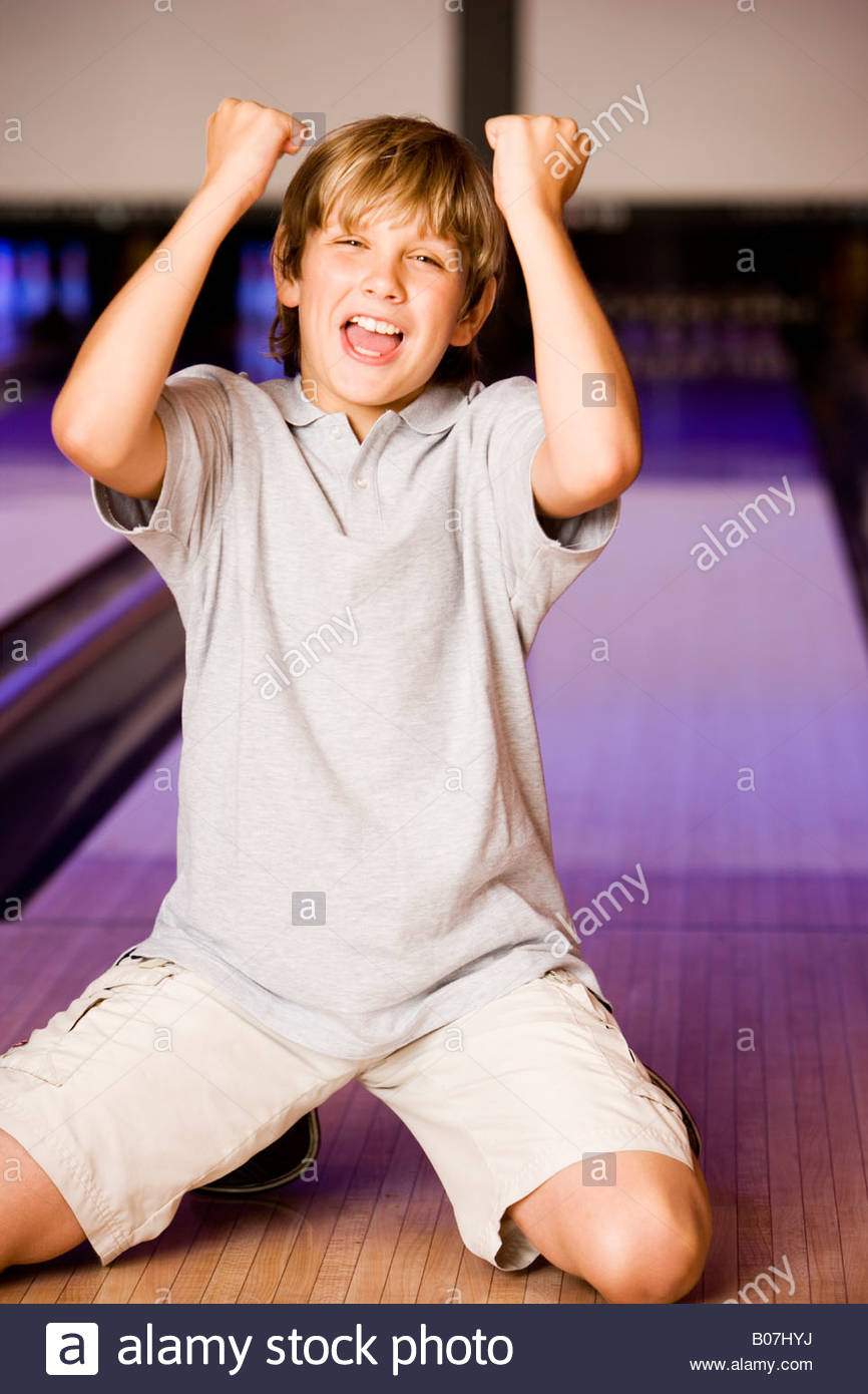 Boy in a bowling alley making victory salute - Stock Image