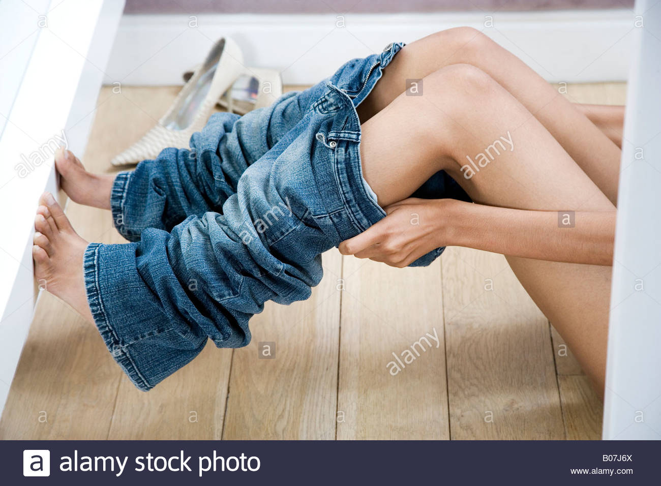 Woman trying on jeans in the changing room of a shop - Stock Image