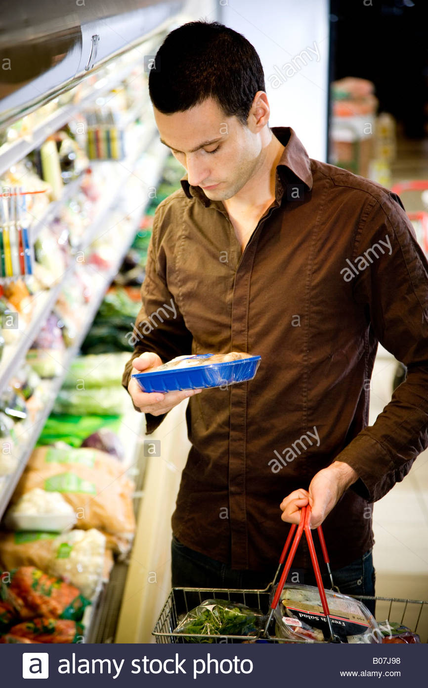 Man reading the label on food packaging in a supermarket - Stock Image