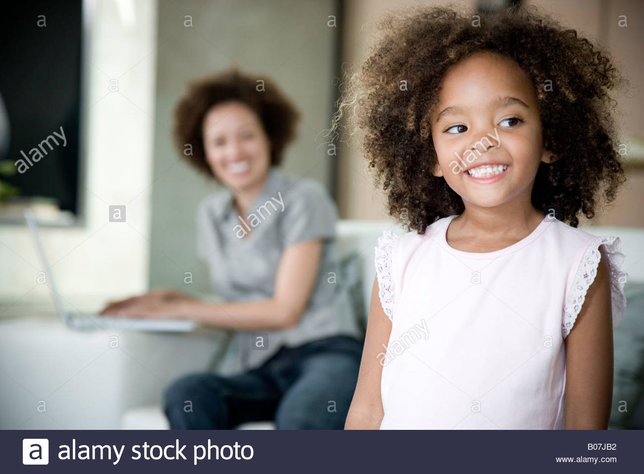 Little girl at home smiling, whilst her mother works on a laptop in the background - Stock Image