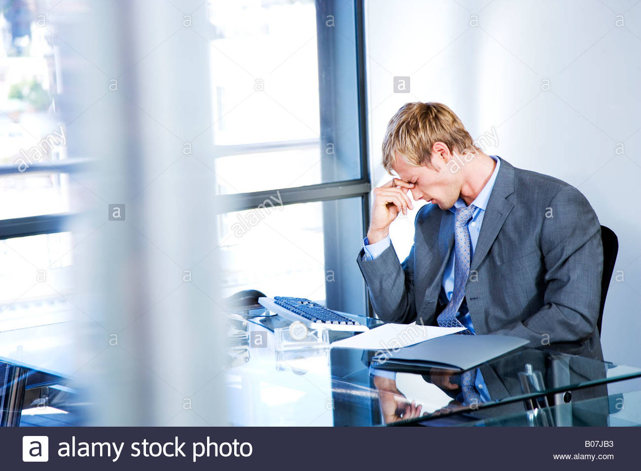 Businessman looking stressed in a modern office - Stock Image