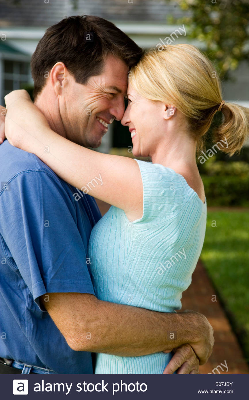A couple embracing and on the verge of a kiss, standing on the garden path outside their new home, - Stock Image