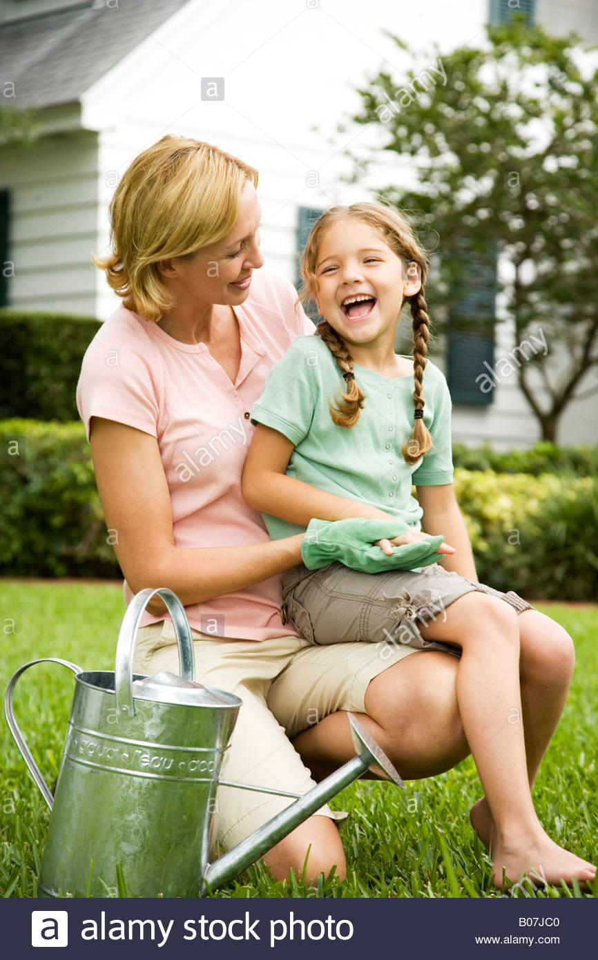 Girl Sitting On Mother S Lap Laughing In The Garden Stock