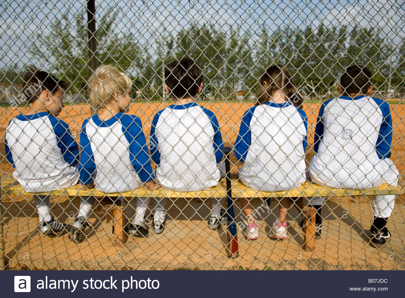 Rear view of a little league baseball team sitting on bench - Stock Image