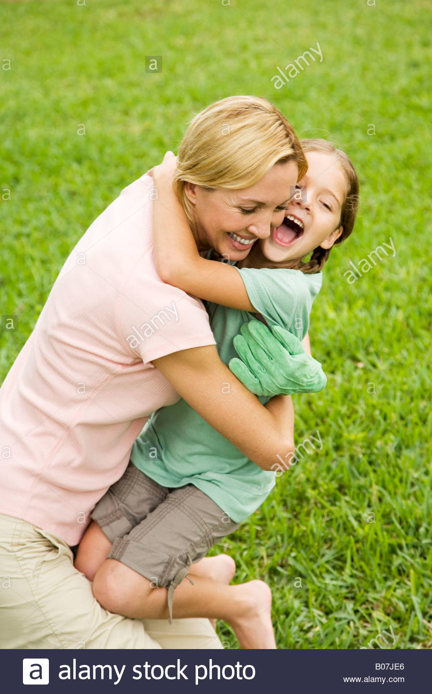 mother and daughter hugging in the garden - Stock Image