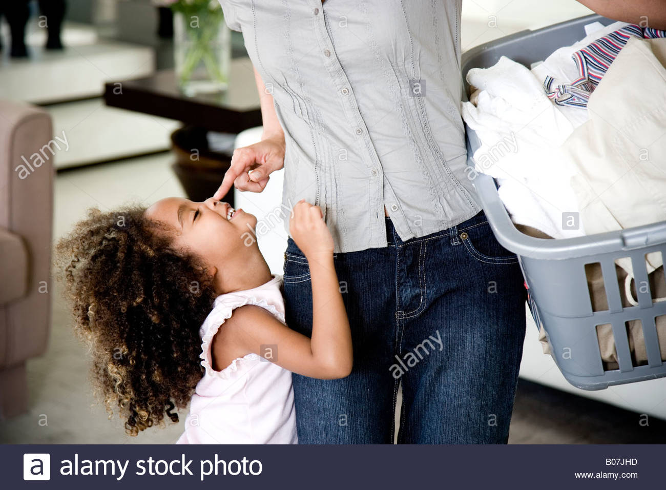Mother playing with young daughter, carrying the washing - Stock Image