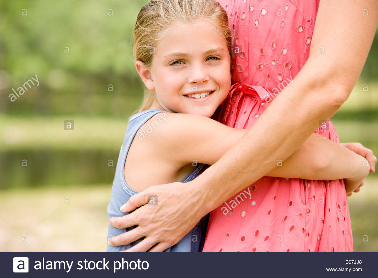 girl hugging woman around the waist - Stock Image