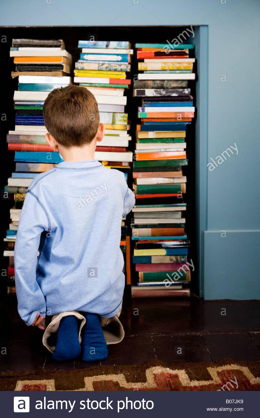 Little Boy Looking For Book In Bookshelf