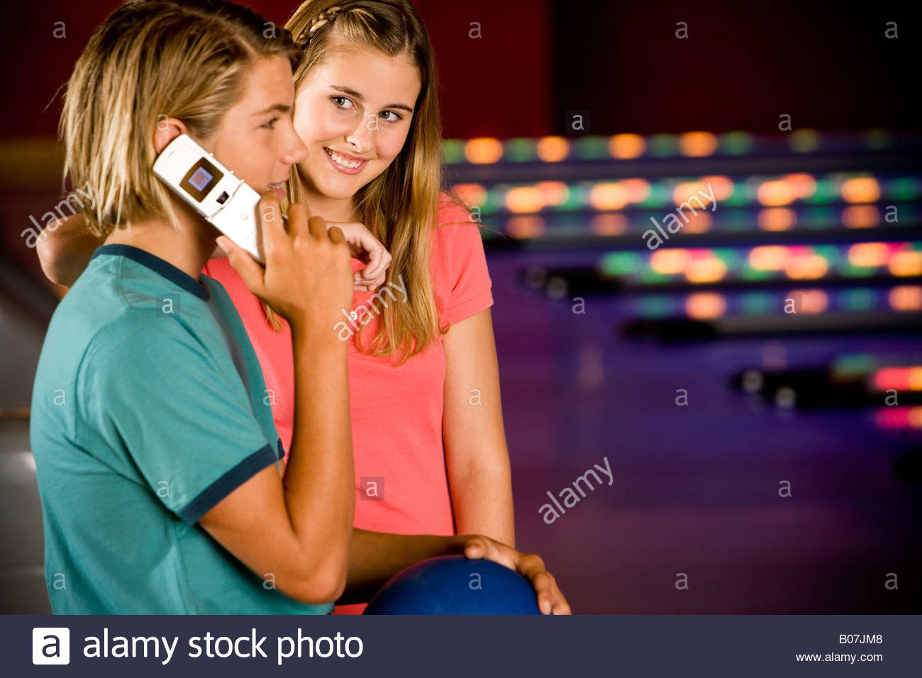 Teenage boy and girl in a bowling alley, boy talking on mobile phone - Stock Image