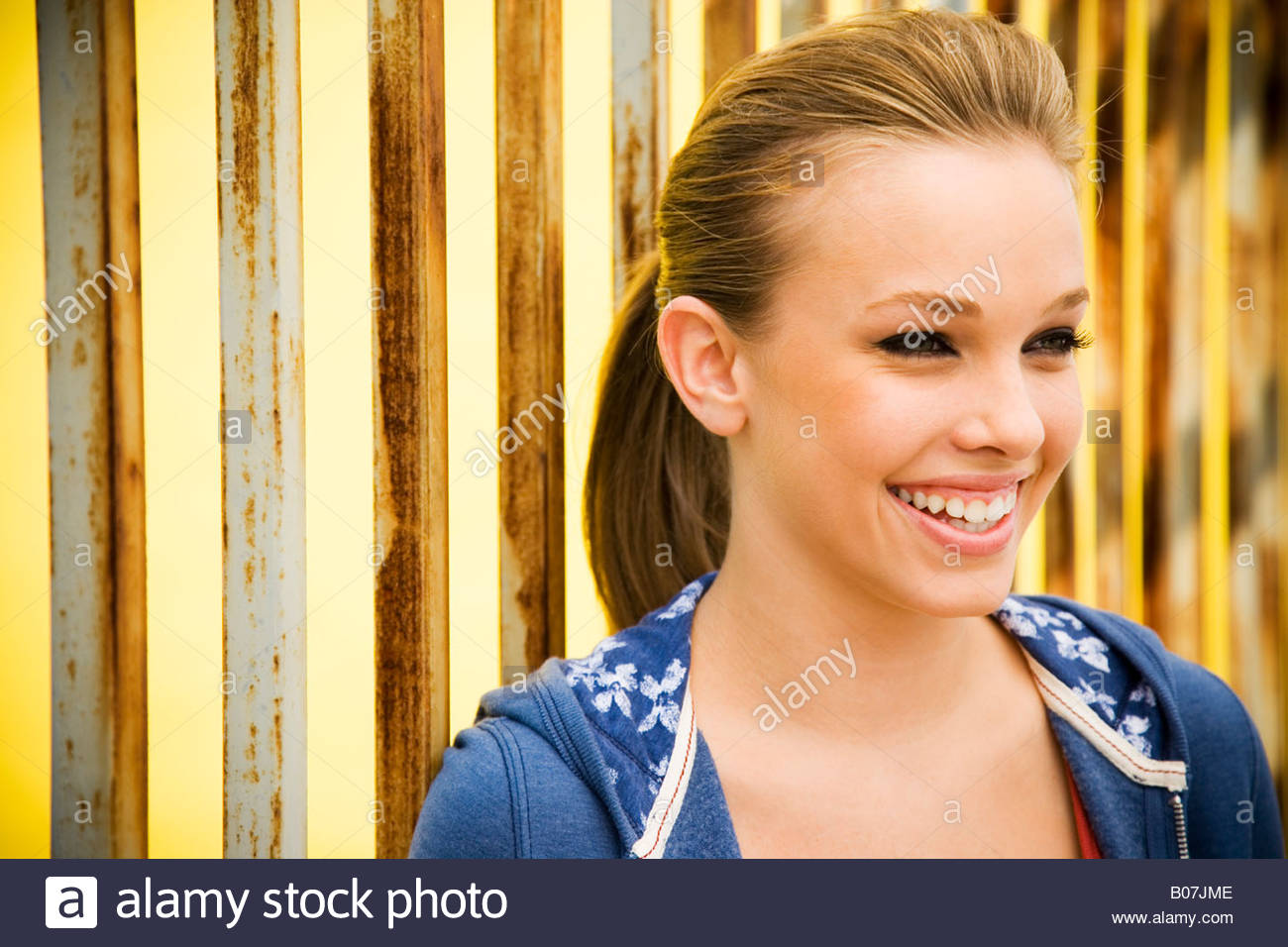 Portrait of a girl leaning against railing bars - Stock Image