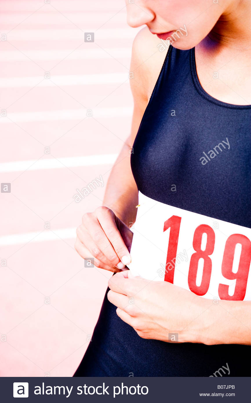 Close in crop of a female athlete attaching her competitors number - Stock Image