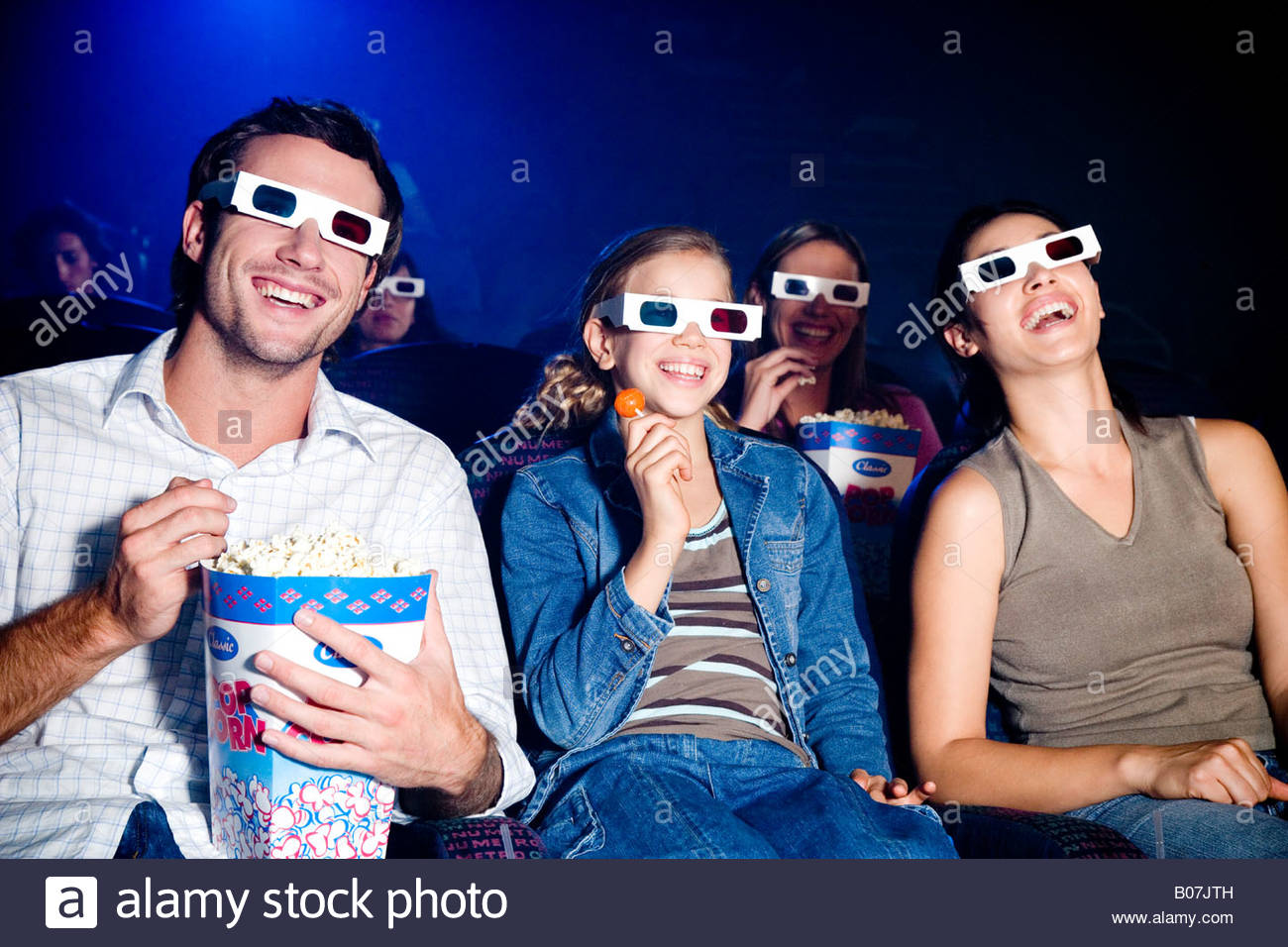 Family at the cinema watching a film through 3-D glasses - Stock Image