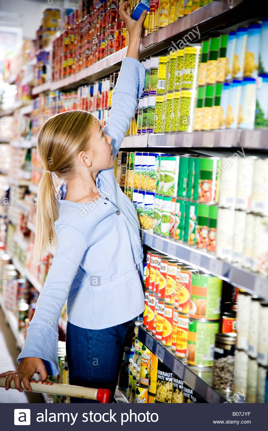 Young girl reaching up to get something off of a supermarket shelf - Stock Image