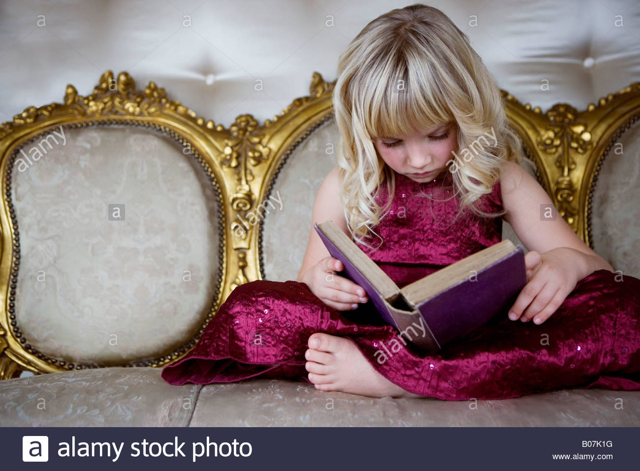 Little girl in a party dress reading a book - Stock Image