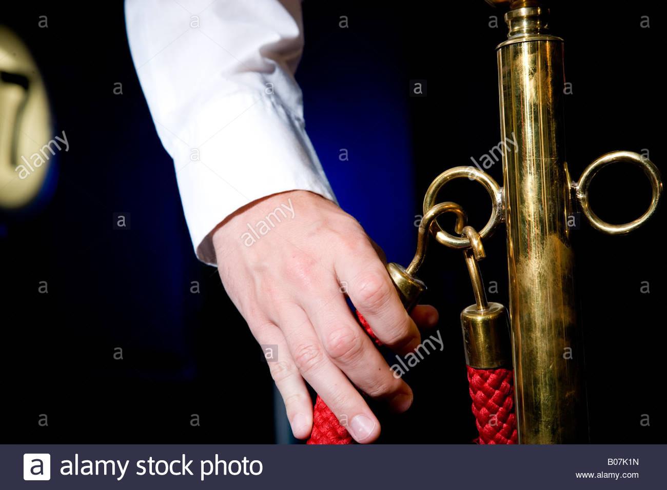 Cinema usher's hand holding red cordon - Stock Image