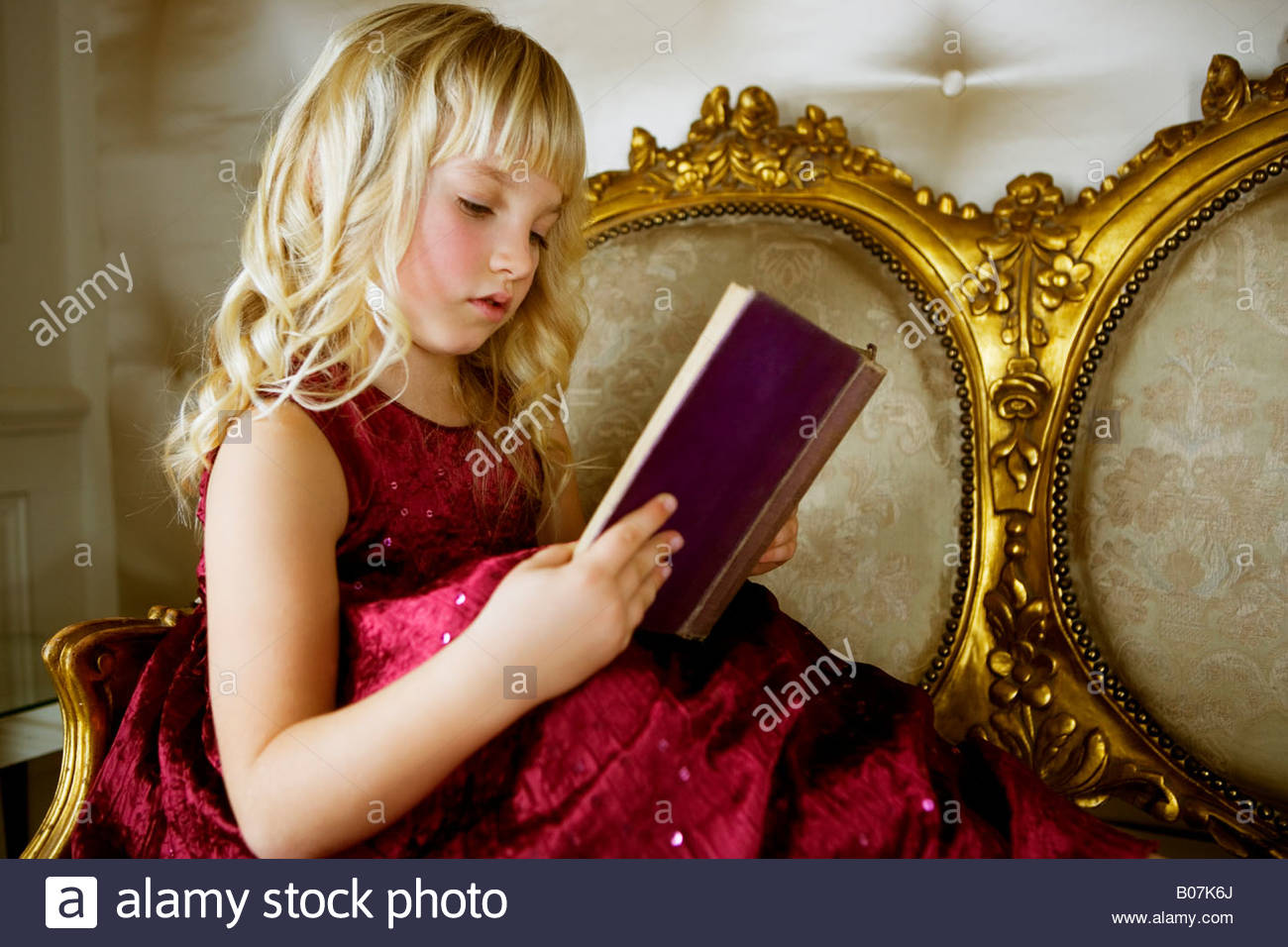 Little girl in a party dress, reading a book - Stock Image