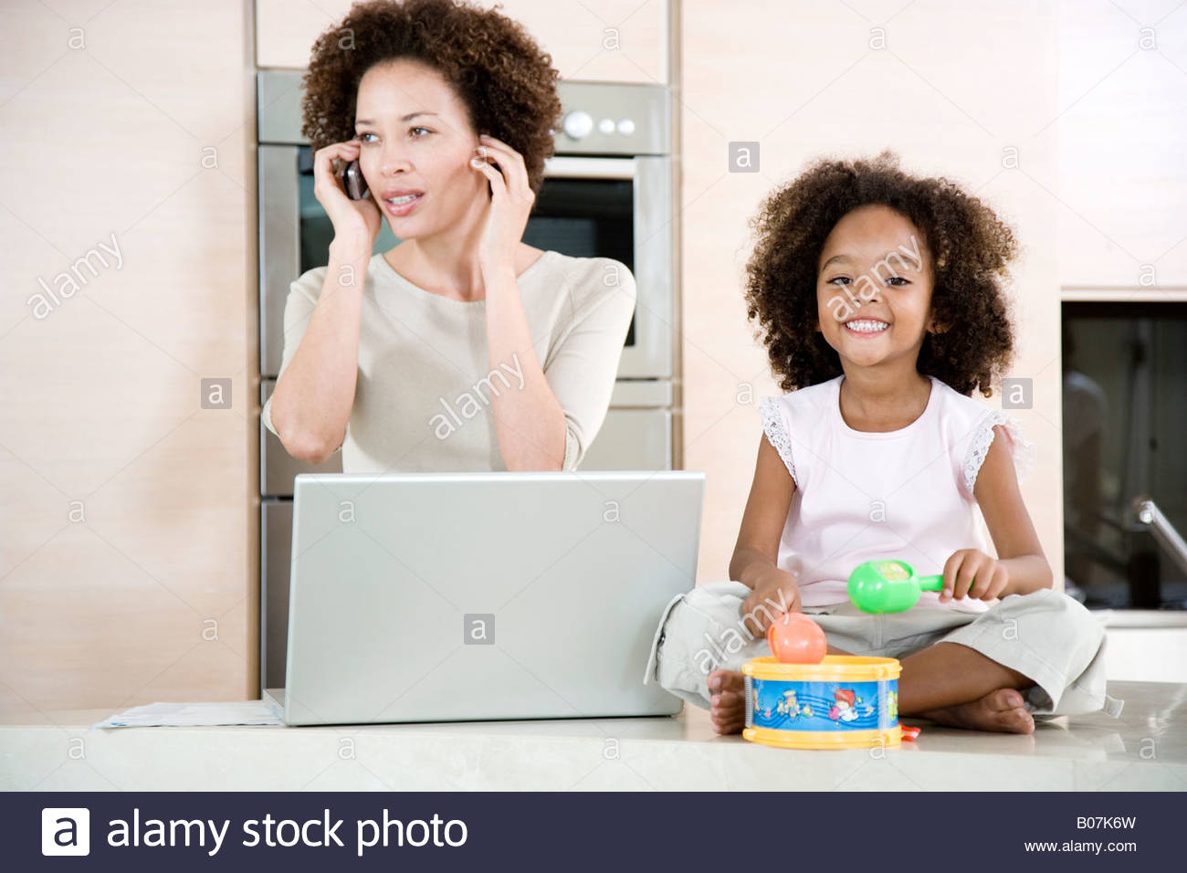 Stressed mother working from home while daughter plays a toy drum - Stock Image