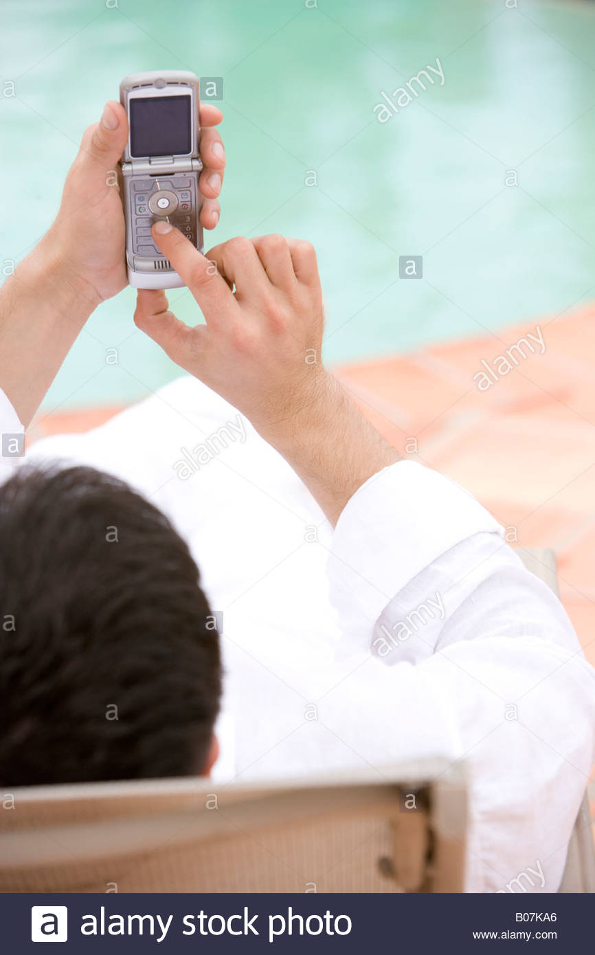 Man sitting by a swimming pool, using a mobile phone - Stock Image