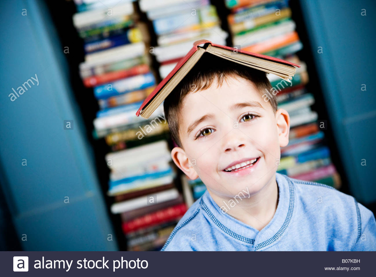 little boy with book on his head Stock Photo