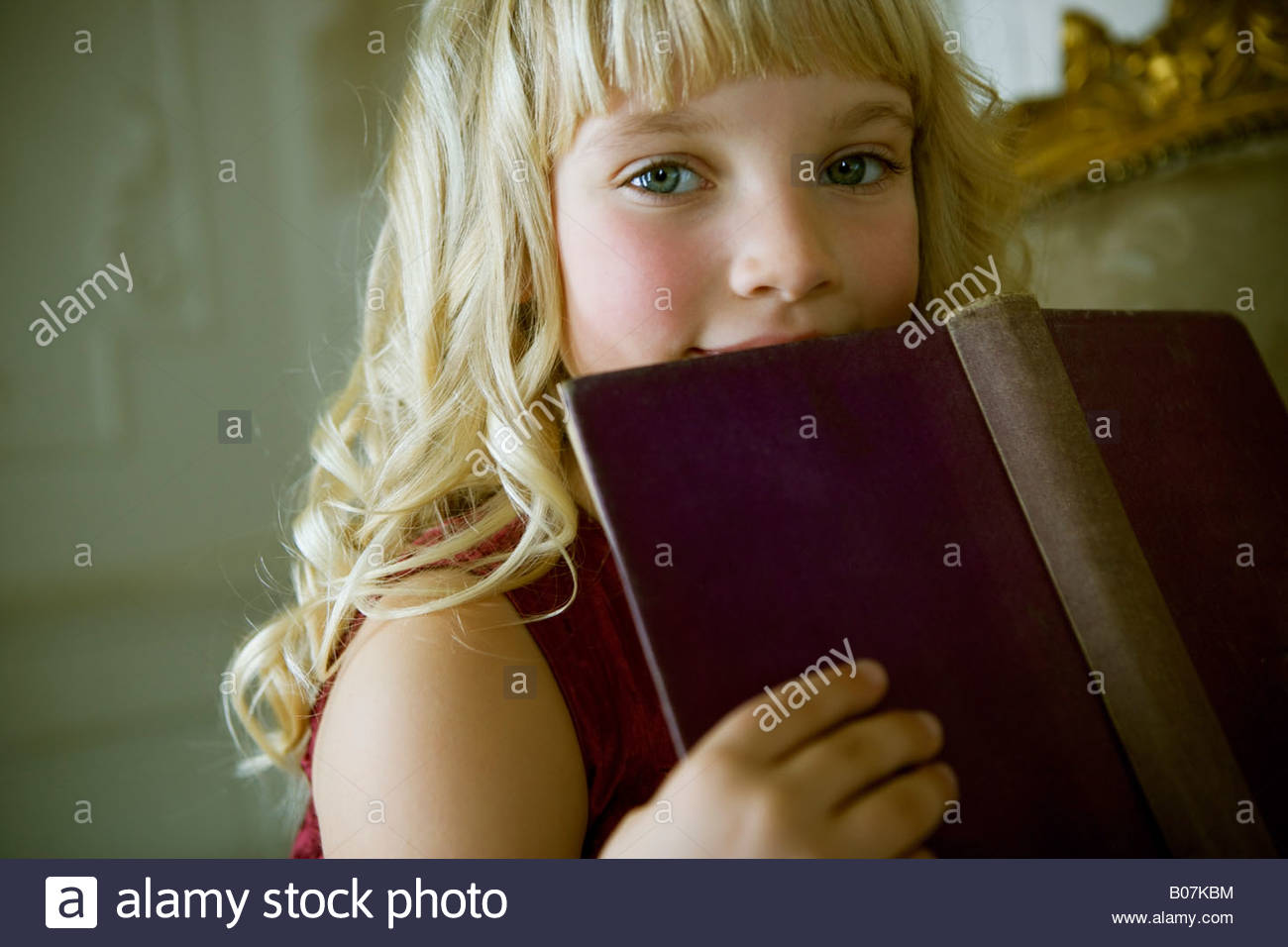Portrait of a little girl reading a book - Stock Image
