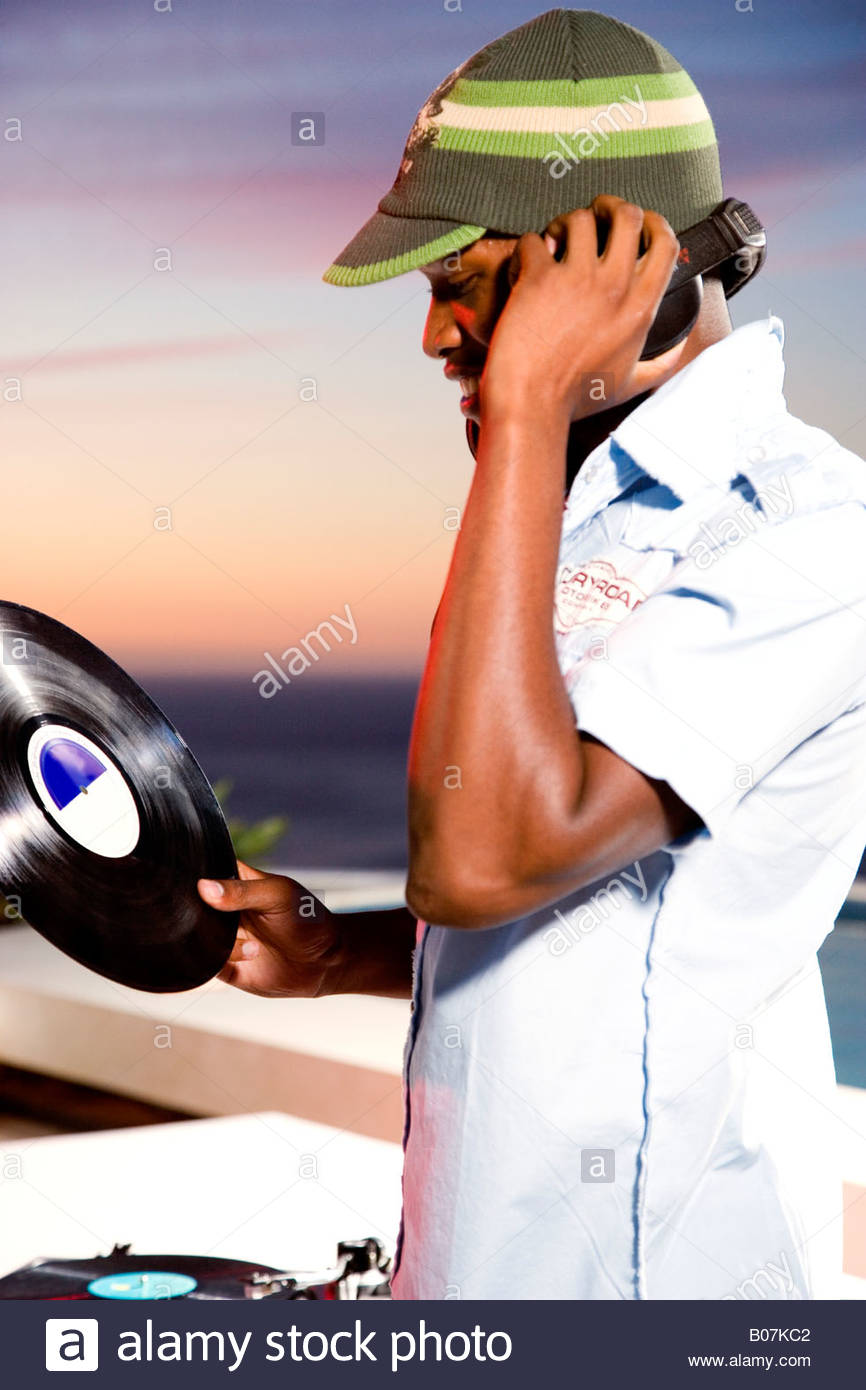 A dj holding a record at an outdoor party at sunset - Stock Image