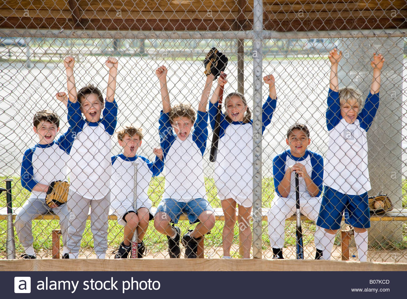 Little league baseball team cheering behind wire fence - Stock Image