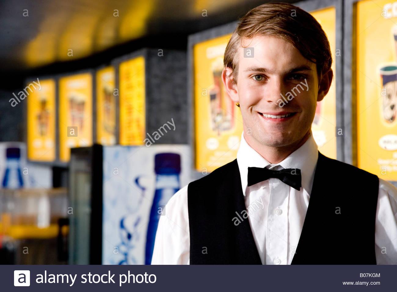 Smartly dressed usher at the cinema smiling - Stock Image