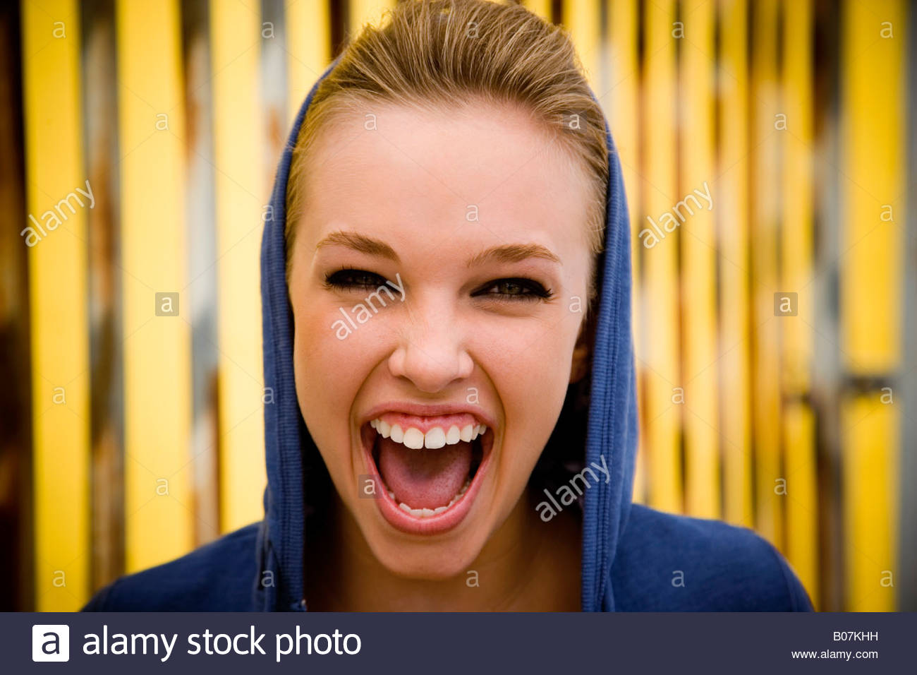 Portrait of a girl leaning against railing bars screaming - Stock Image