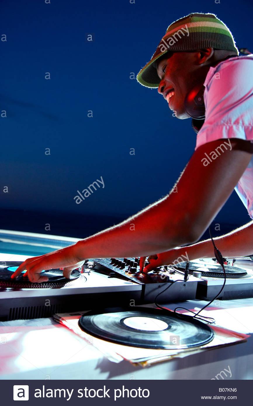 DJ mixing on decks outside Stock Photo
